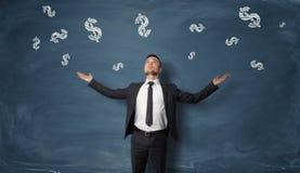 De zakenman met zijn handen hief het kijken op dollartekens die op vallen Stock Fotografie