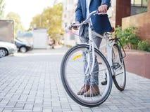 De zakenman nam de fiets en gaat met hem werken stock afbeeldingen