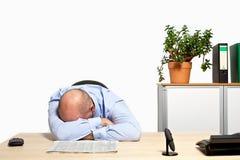 De zakenman neemt een dutje in zijn bureau Royalty-vrije Stock Afbeeldingen