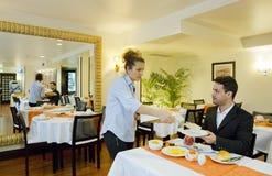 De zakenman neemt ontbijt in hotel royalty-vrije stock afbeelding