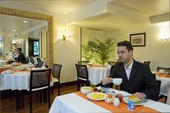 De zakenman neemt ontbijt in hotel stock foto