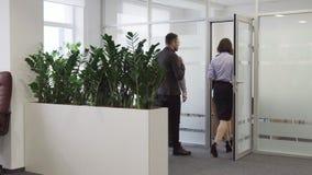 De zakenman nodigt een team van bedrijfsmensen uit om vergaderzaal op kantoor in te gaan stock footage