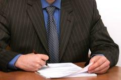 De zakenman ondertekent een document stock foto