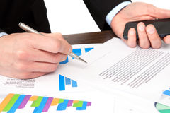 De zakenman ondertekent een document op het kantoor en houdt de telefoon Stock Afbeeldingen