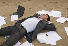 De zakenman ontspant op het strand Stock Afbeeldingen