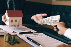 De zakenman overhandigde het huis model en nieuwe huiseigenaar die geld geven aan onroerende goederen handel royalty-vrije stock afbeeldingen