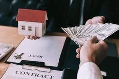 De zakenman overhandigde het huis model en nieuwe huiseigenaar die geld geven aan onroerende goederen handel royalty-vrije stock foto