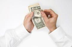 De zakenman overhandigt tellend geld Stock Foto