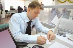 De zakenman in overhemd neemt nota's bij lijst Stock Afbeeldingen