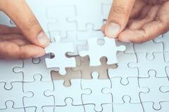 De zakenman probeert om tweedelig van puzzel te verbinden Royalty-vrije Stock Afbeeldingen