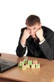 De zakenman probeert samenstelt blokken met brieven Stock Foto