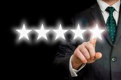 De zakenman richt vijf sterren - overzicht en het schatten concept Stock Foto's