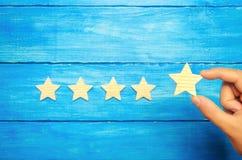 De zakenman` s hand houdt de vijfde ster Een nieuwe ster, voltooiing Het concept de classificatie van hotels en restaurants, Eva stock afbeeldingen