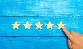 De zakenman` s hand richt aan de vijfde ster Een nieuwe ster, voltooiing Het concept de classificatie van hotels en restaurants, stock foto
