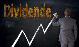 De zakenman schrijft Dividende in Duits dividend op bord stock fotografie