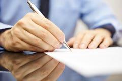 De zakenman schrijft een brief of ondertekent een overeenkomst