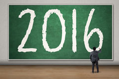 De zakenman schrijft nummer 2016 op het bord Stock Foto
