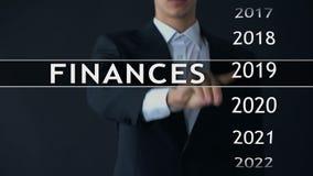 De zakenman selecteert de financiën van 2021 rapporteert over het virtuele scherm, geldstatistieken stock videobeelden