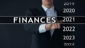 De zakenman selecteert de financiën van 2023 rapporteert over het virtuele scherm, geldstatistieken stock video