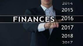 De zakenman selecteert de financiën van 2018 rapporteert over het virtuele scherm, geldstatistieken stock footage