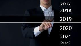De zakenman selecteert het jaar van 2019 in virtueel menu, onderzoek naar gegevens, bedrijfsgeschiedenis stock foto