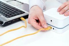 De zakenman sluit zijn laptop aan de mobiele WiFi-router aan Royalty-vrije Stock Fotografie