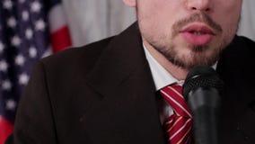 De zakenman spreekt in microfoon stock footage