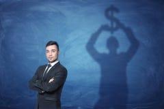 De zakenman status van en schaduw op het bord achter hem het teken van de holdingsdollar boven zijn hoofd Stock Afbeeldingen