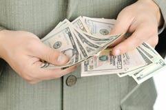 De zakenman telt geld in handen. Stock Foto