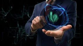 De zakenman toont conceptenhologram 3d boom op zijn hand