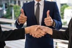 De zakenman toont duim en twee onderneemster het schudden handen voor het aantonen van hun overeenkomst aan tekenovereenkomst of  Royalty-vrije Stock Afbeelding