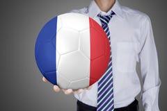 De zakenman toont een bal met de vlag van Frankrijk Royalty-vrije Stock Afbeeldingen