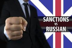 De zakenman toont een vuist tegen de achtergrond van de Engelse vlag en een inschrijving van sancties tegen Rusland Royalty-vrije Stock Foto's