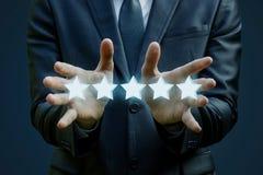 De zakenman toont vijf sterren het schatten Royalty-vrije Stock Afbeeldingen