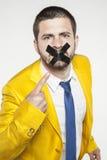De zakenman toont zijn verzegelde lippen, een belofte van geheimhouding royalty-vrije stock fotografie