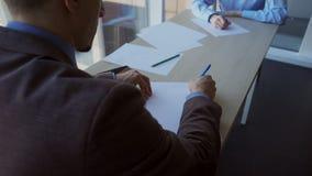 De zakenman treft aan de presentatie met zijn vrouwelijke collega voorbereidingen die de regeling trekken stock footage
