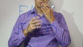 De zakenman van de snel voedselinschrijving schrijft op glas4k video stock video