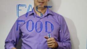 De zakenman van de snel voedselinschrijving schrijft op glas video4k stock video