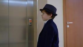 De zakenman van de kindjongen wacht lift in zijn bureau Het levensparodie van de volwassene stock footage