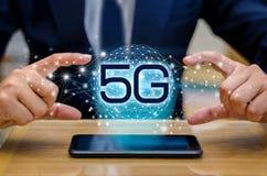 De zakenman van de telefoon5g Aarde verbinden kelnershand wereldwijd houdend een lege digitale tablet aan slim en 5G conc netwerk stock fotografie