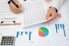 De zakenman van de werkplaats Contracten, grafieken, en grafieken op het bureau stock fotografie