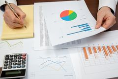 De zakenman van de werkplaats Contracten, grafieken, en grafieken op het bureau stock foto