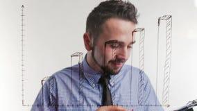 De zakenman vergelijkt gegevens van documenten in grafiek stock footage