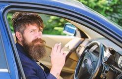 De zakenman vermoeide na harde onderhandelingen rokend voertuig Het roken verboden in privé voertuigen Mensen gebaarde zakenman stock foto