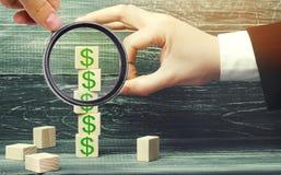 De zakenman verwijdert een kubus met een beeld van dollars financieel stock foto's