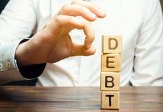 De zakenman verwijdert houten blokken met de woordschuld Vermindering of het herstructureren van schuld Faillissementsaankondigin stock afbeeldingen