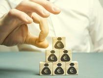 De zakenman verwijdert de kubus met het beeld van de euro hoofdafvloeiing druk op kleine ondernemingen Faillissement economisch royalty-vrije stock afbeeldingen