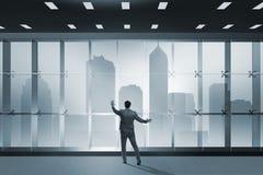 De zakenman voor bureauvenster het denken aan nieuwe uitdagingen stock foto's