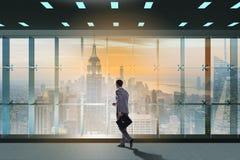 De zakenman voor bureauvenster het denken aan nieuwe uitdagingen stock afbeelding