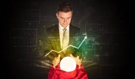 De zakenman voorspelde de toekomst van de effectenbeurs met een magische bal stock foto